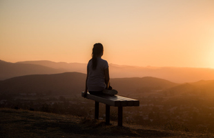 Woman sitting on bench, meditating.